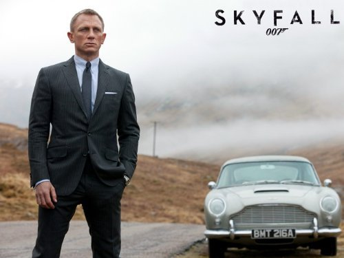 Daniel Craig standing on a road with silver car in the background. Skyfall poster from Amazon.com.